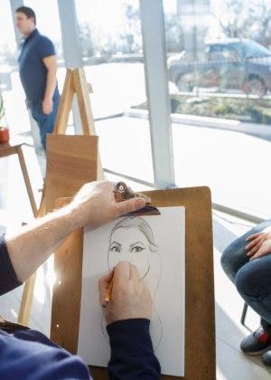Художник рисует шарж карнадашами.